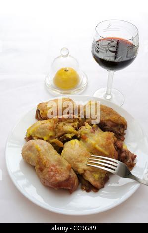 Gebratene Hähnchenschenkel auf weißen Teller, Glas Wein und Zitrone auf weißem Stoff Hintergrund. - Stockfoto