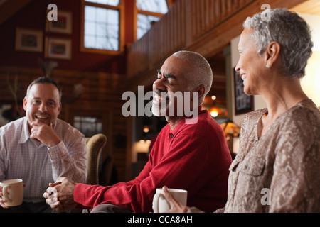 Ältere Freunde lachen zusammen im Wohnzimmer