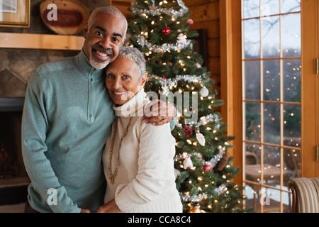 Reifen paar umarmt von Weihnachtsbaum, Porträt - Stockfoto