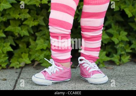 Beine eines Kleinkindes in rosa gestreifte leggings - Stockfoto