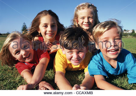 Grinsende Kinder Verlegung Gras zusammen - Stockfoto