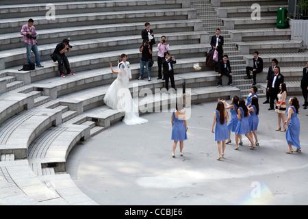 Eine Braut werfen ihren Blumenstrauß zu einer Gruppe von Brautjungfern Olympischen Platz an der Hong Kong Park, - Stockfoto