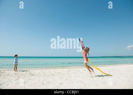 Junge Drachen am Strand, Mädchen, springen, fangen - Stockfoto