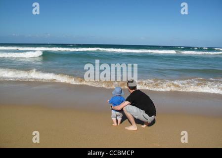 Vater und Kind am Strand, Blick auf See - Stockfoto