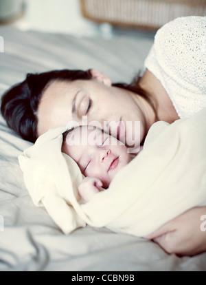 Mutter und neugeborenes Baby schlafend im Bett - Stockfoto