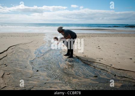 Vater und Kind betrachten wellige Sand am Strand - Stockfoto
