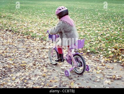 Kleinen Mädchen Reiten Fahrrad in Herbstlandschaft, Rückansicht - Stockfoto