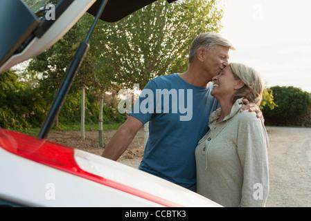 Älteres paar stehen neben Auto, Mann küssen Frau Stirn - Stockfoto