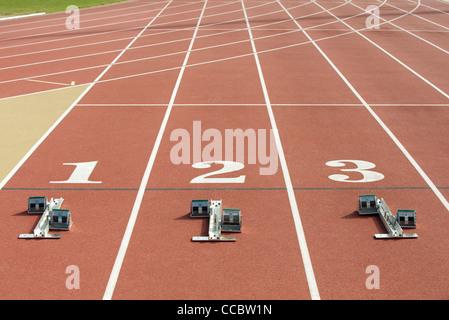 Startblöcke an Startlinie auf Laufband - Stockfoto