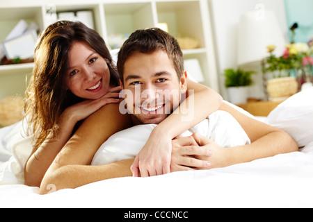 Glückliches junges Paar im Bett liegen und Blick in die Kamera - Stockfoto