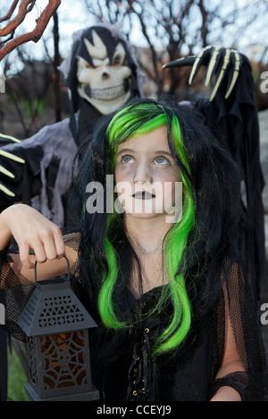 Kleine Hexe mit Laterne mit jungen hinter dem Sensenmann-Kostüm - Stockfoto