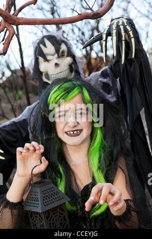 Kleine Hexe mit Laterne mit Person kostümiert als Sensenmann steht im Hintergrund - Stockfoto