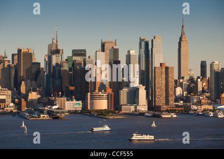 Segelboote und Fähren auf dem Hudson River mit der Midtown Manhattan Skyline im Hintergrund - Stockfoto