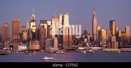 Sonnenuntergang über der Skyline von Midtown Manhattan malt das Wolkenkratzer-gold - Stockfoto