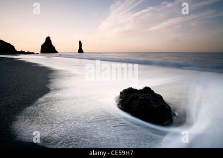 Wellen im ganzen schwarzen vulkanischen Felsnadeln entlang der Vik in Island - Stockfoto