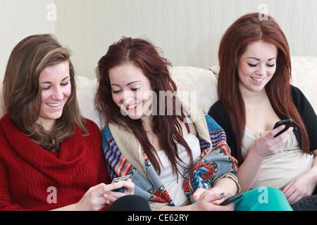 Drei generation z Jugendmädchen Freunde im Alter von 15 Jahren in einem Lachen von Fotos auf einem Mobiltelefon, - Stockfoto