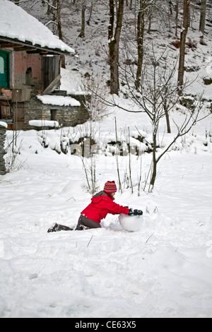 Mädchen spielen im Schnee und bauen einen Schneemann - Stockfoto