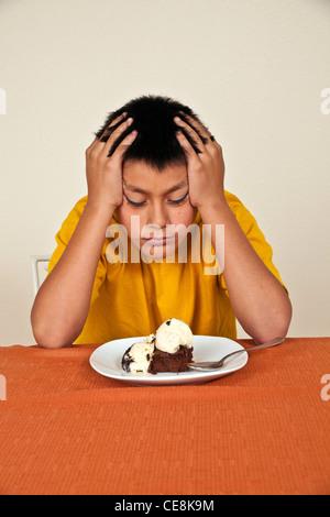 Willensstark hartnäckige 10-11 Jahre alten Hispanic junge am Tisch sitzen will nicht essen. Multi ethnische Vielfalt - Stockfoto