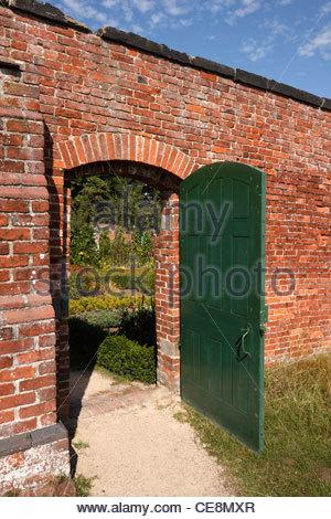 Grüne Tür öffnen in roten Backsteinmauer führt zum Garten Küche Calke Abbey, Ticknall, Derbyshire, England, UK - Stockfoto