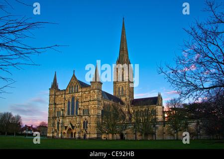 Dämmerung fällt über der Westfront und Turm der mittelalterlichen Kathedrale von Salisbury, Wiltshire, England, - Stockfoto
