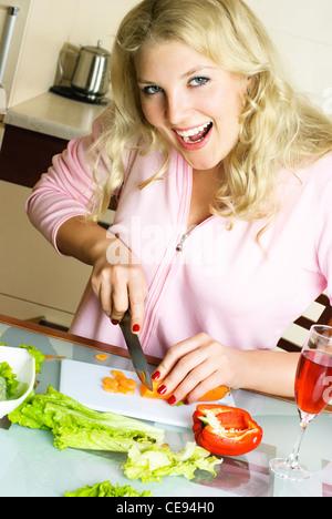 begeistert junge Frau machen Salat und Karotten schneiden zu Hause in der Küche - Stockfoto