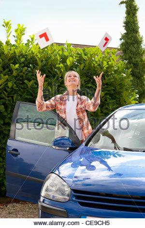 Lächelnde junge Frau wirft der Lernenden Vignette in Luft neben Auto - Stockfoto