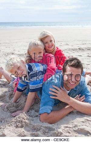 Porträt der lächelnden Vater mit Töchtern und seinem Sohn am Sonnenstrand - Stockfoto