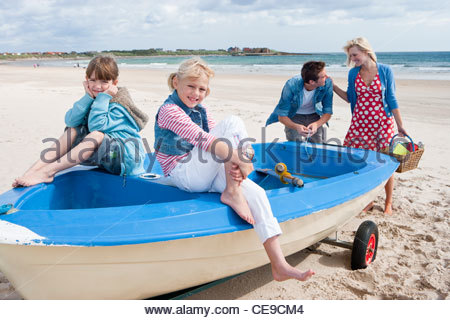Happy Family im Boot am Strand - Stockfoto