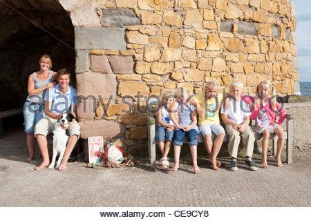 Porträt der Familie mit Hund sitzt vor Gebäude aus Stein - Stockfoto