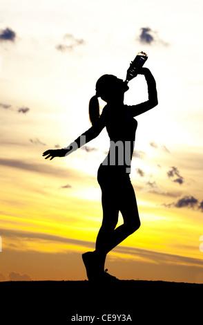 Silhouette einer Frau Trinkwasser auf dem Hügel gegen gelben Himmel mit Wolken - Stockfoto