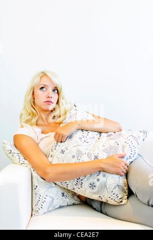 Nachdenkliche schöne blonde Frau umarmt Kissen auf Sofa - Stockfoto