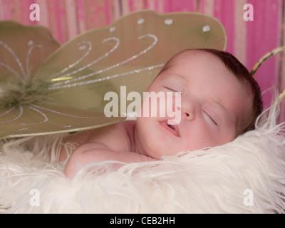 Nahaufnahme der ein wunderschönes neugeborenes Mädchen mit grüne Feenflügel auf einer Pelz Decke. Sie sieht aus - Stockfoto