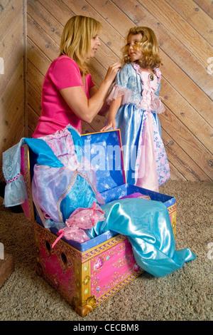Mit Hilfe ihrer Mutter zieht eine drei Jahre alte blonde Mädchen schicke Klamotten aus ihrer Schatztruhe zu Hause - Stockfoto
