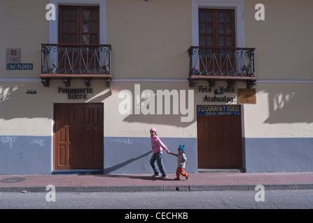 Eine ältere Schwester und hält die Hand ihres jüngeren Bruders, wie sie entlang einer Quito, Ecuador-Straße im späten - Stockfoto