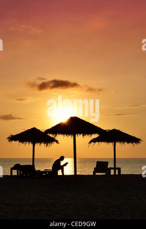 Person ein Buch am Strand bei Sonnenuntergang, silhouette, Kib Hotel, Koh Kho Khao Island, Süd-Thailand - Stockfoto