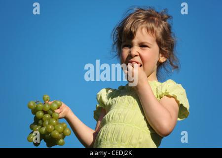 Mädchen isst Traube gegen blauen Himmel - Stockfoto