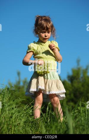 Mädchen isst Traube in Rasen gegen blauen Himmel - Stockfoto