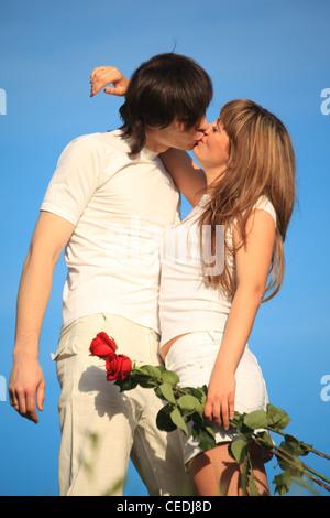 Mädchen mit Rosenstrauß küsst Mann gegen Himmel - Stockfoto