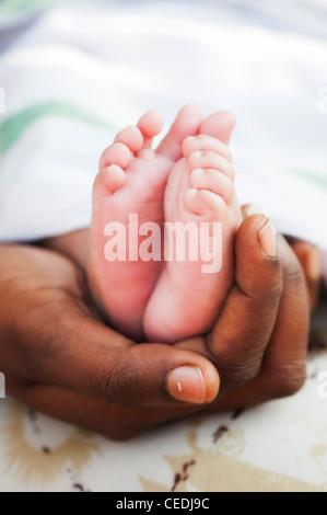 Indische Mutter hielt ihren Neugeborenen nackten Füßen. Andhra Pradesh, Indien. Selektiven Fokus. - Stockfoto
