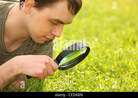 junger Mann schaut durch Lupe auf Wiese - Stockfoto