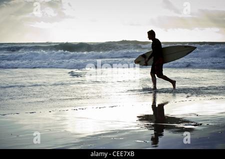 Silhouette eines Surfers zu Fuß mit seinem Surfbrett entlang des Strandes mit stürmischen Wolken im Hintergrund, - Stockfoto