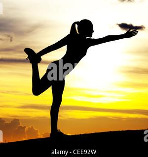 Silhouette einer jungen Frau praktizieren Yoga auf dem Hügel gegen gelben Himmel mit Wolken bei Sonnenuntergang - Stockfoto