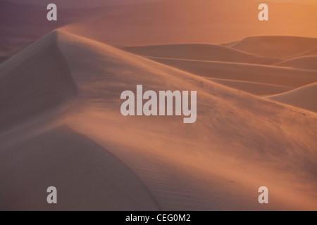 Wehenden Sand bei Sonnenaufgang in den flachen Mesquite Dünen, Death Valley, CA - Stockfoto