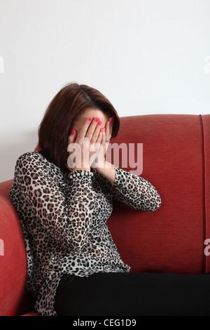 Junge Frau sitzt allein mit ihr Gesicht mit beiden Händen bedeckt. - Stockfoto