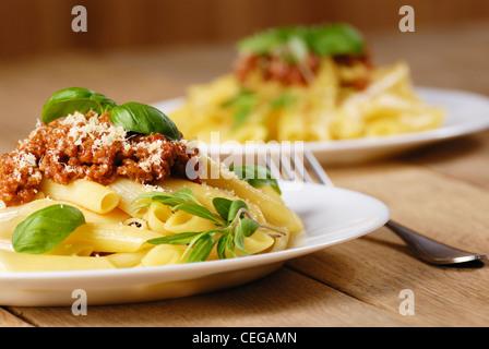 Rigatoni-Nudeln mit Rindfleisch-Tomatensauce in die weiße Platte - Stockfoto