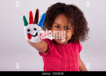 Kleine afrikanische Asiatin mit bemalten Händen in bunten Farben - Stockfoto