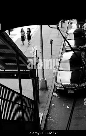 zwei Mädchen gehen, teilen Eis am Weg zum Bahnhof Stockfoto