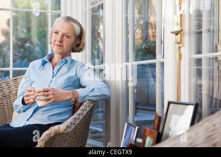 Ältere Frau mit heißen Getränken entspannen - Stockfoto