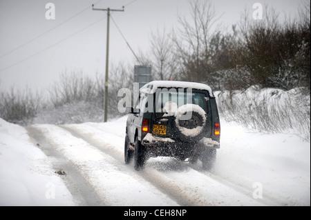 Land Rover 4 x 4 verhandelt einen Hügel in den schneebedeckten Bedingungen in Gloucestershire UK - Stockfoto