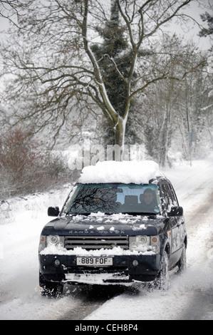Ein Range Rover 4 x 4 verhandelt einen Hügel in den schneebedeckten Bedingungen in Gloucestershire UK - Stockfoto